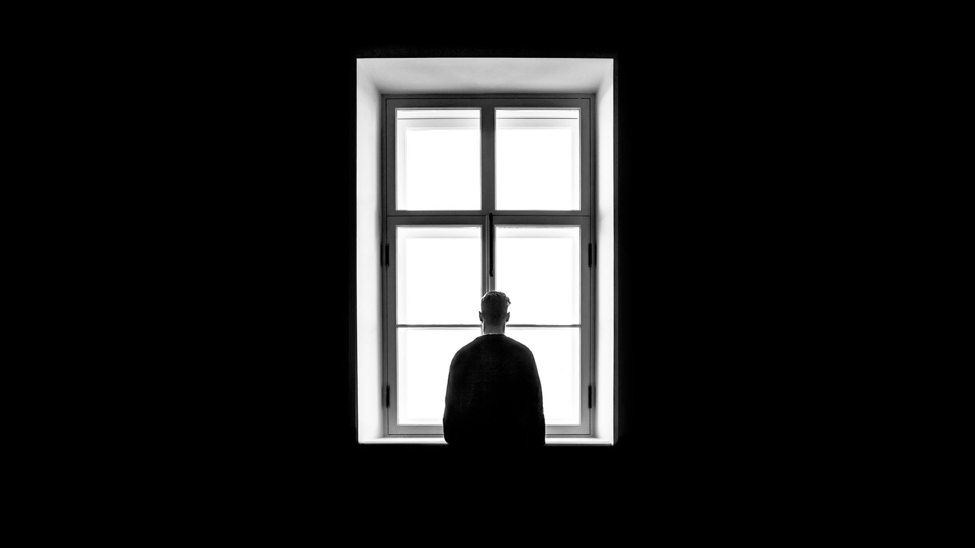 lonely man in black room with window